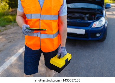 Car mechanic holding a box of tools and stands in front of car. Suitcase with tools and instruments for diagnosis in hands of car mechanic on background of a broken car. Mobile roadside assistance
