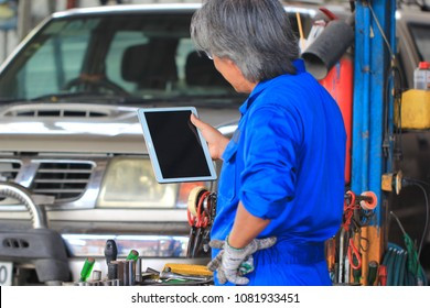 Car mechanic holding digital tablet in auto repair service.