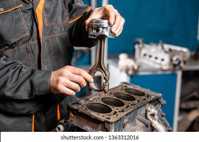 Car mechanic holding a new piston for the engine, overhaul.. Engine on a repair stand with piston and connecting rod of automotive technology. Interior of a car repair shop.
