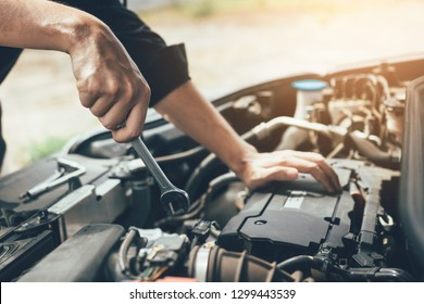 Car mechanic is holding a wrench ready to check the engine and maintenance.