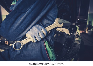 Car Mechanic with Huge Wrench Preparing For Car Maintenance and Big Fix.