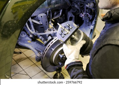 Car mechanic ian work with an innovative system of air suspension for tuned car. Engineer examining air suspension system before install