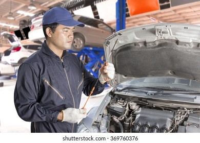 Car mechanic Inspection of the engine oil by guage at auto repair shop