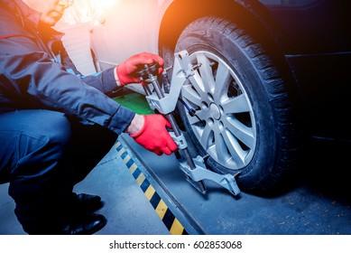 Car mechanic installing sensor during suspension adjustment. Wheel alignment work at repair service station