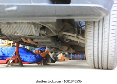 Car mechanic lying down and working under car in auto repair service