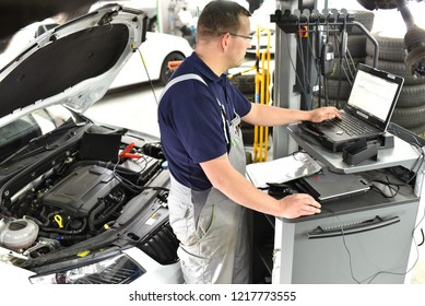 car mechanic maintains a vehicle with the help of a diagnostic computer - modern technology in the car repair shop