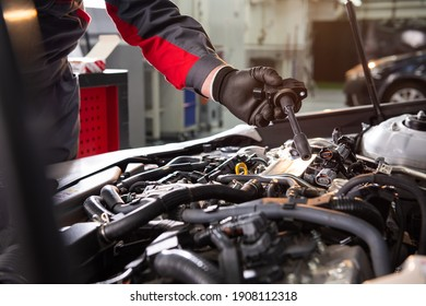 the car mechanic makes diagnostics of the car in the engine. car service and audit by an employee in a large car service. candle replacement