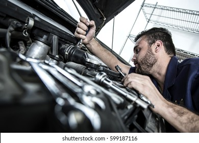 Car mechanic man at the garage fixing the engine