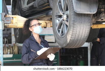 car mechanic on protective mask anti coronavirus and they are fixing car engine in garage