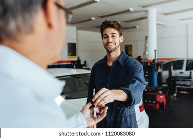 Car mechanic passing car keys to the car owner after repairing his vehicle. Mechanic giving car key to customer after servicing at garage.