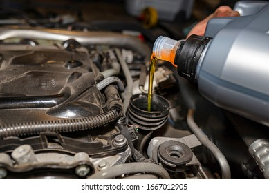 Car mechanic pours new car oil into the engine from a plastic tank in a car workshop.