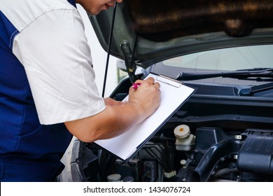 The car mechanic is recording the checklist of the car's bad condition.