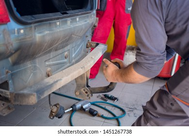 Car mechanic removing old tow hook with his hands. Car repair concept
