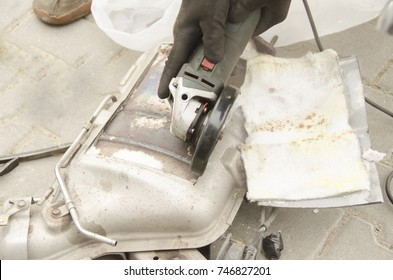 Car mechanic is remowing diesel particulate filter, DPF of the car in the repair shop.