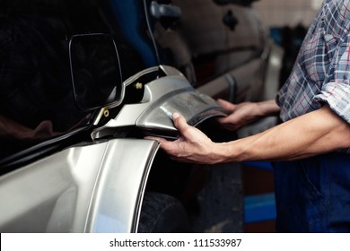 Car mechanic repairing broken part