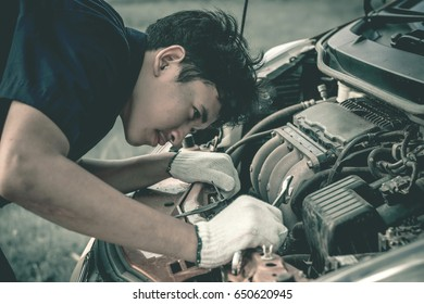 Car mechanic repairing a car engine.