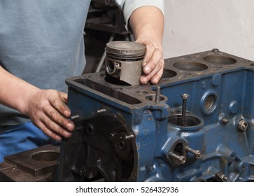 Car mechanic repairing an internal combustion engine