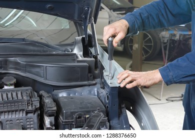 car mechanic repairs car bodywork of a vehicle after a traffic accident