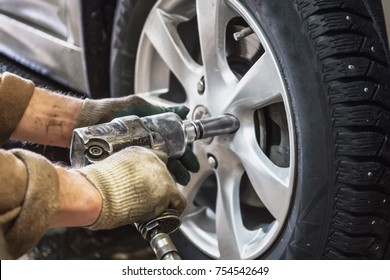 Car mechanic replace car wheels of lifted automobile by pneumatic wrench at repair service shop garage station, close up
