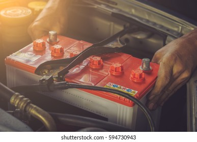 A car mechanic replaces a battery / soft focus picture