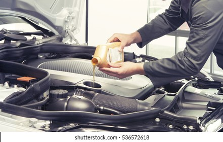 Car mechanic replacing and pouring oil into engine at maintenance repair service station