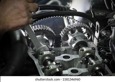 Automechaniker, der den Zahnriemen an der Nockenwelle des modernen Motors mithilfe eines Schlüsselwerkzeugs ersetzt