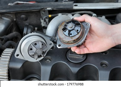 Car mechanic replacing water pump of modern engine