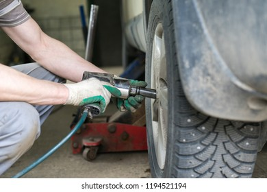 car mechanic screwing or unscrewing car wheel of lifted automobile at repair service station