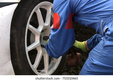 car mechanic screwing or unscrewing car wheel of lifted automobile by pneumatic wrench during car racing
