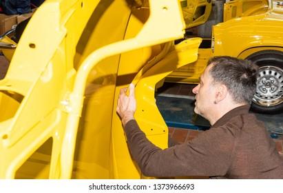 Car mechanic screws car parts together again after restoration - Serie Repair Workshop