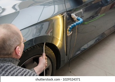 Car mechanic in the car service repairing dents on the car body.