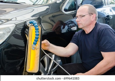 Car mechanic in car service with tools for repairing dents in car body.