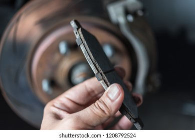 Car mechanic or serviceman checking a disc brake and asbestos brake pads it's a part of car use for stop the car for safety at front wheel this a used old part for change at car garage
