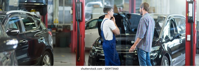 Car mechanic is talking with his client