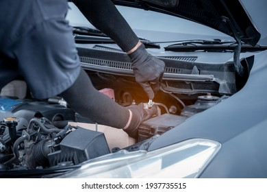 Car mechanic under repairing car  open hood checking electric line car system and clean in car garage service.