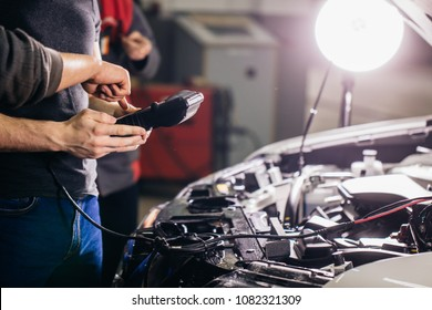 Car mechanic using electrical tool for testing car system in garage repair
