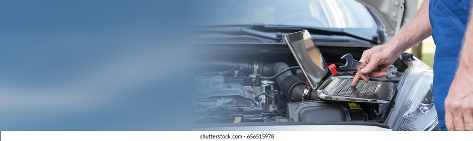 Car mechanic using laptop for checking car engine