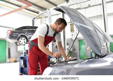 car mechanic in work clothes checks engine from a car in a workshop