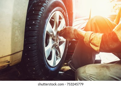 Car mechanic worker doing tire or wheel replacement in garage of repair service station, sunlight effect, toned
