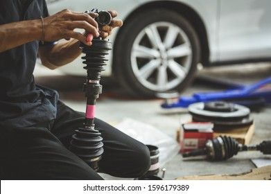 Car mechanic worker repairing Driveshaft and CV Joint Boot in garage shop.