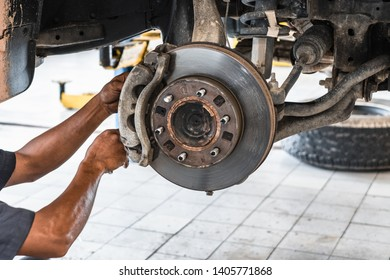 Car mechanic worker woking for reparing and replacing car's disk brake. Car without wheel and tire lifting at auto repair garage shop station.