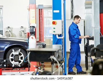 car mechanic working with computer during suspension adjustment and automobile wheel alignment work at repair service station