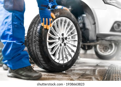 Car mechanic working in garage and changing wheel alloy tire. Repair or maintenance auto service. - Shutterstock ID 1938663823