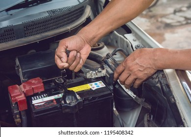 Car mechanic working Install battery with wrench in garage. Repair service.