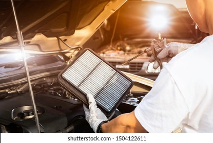 Car mechanic working in repair garage. maintenance checking and cleaning air filter