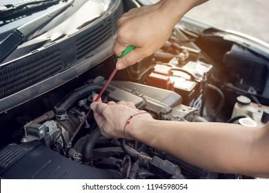 Car mechanic working with screwdriver in garage. Repair service.