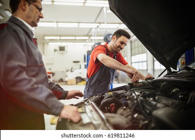 Car mechanics working on car maintenance