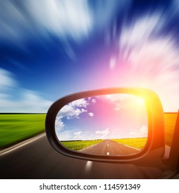 car mirror with blue sky above road