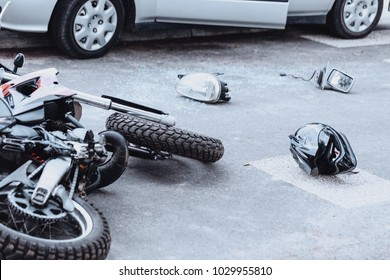Car mirror, headlight, helmet and motorcycle lying on the road after a car crash