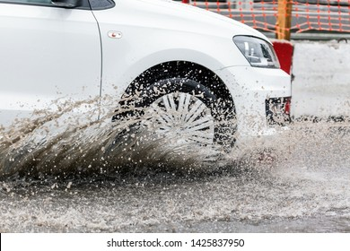 Car motion through big puddle of water splashes from the wheels on the street road. Water splash rain texture